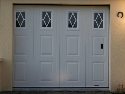 Side sliding garage door with white windows panes and portholes